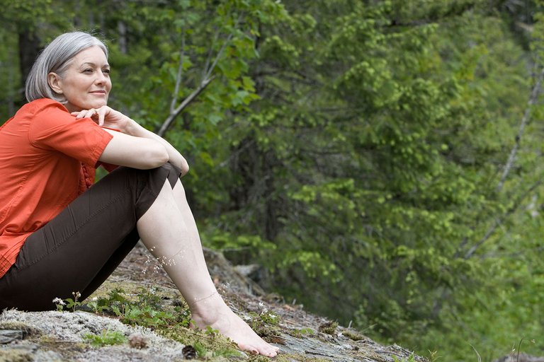 woman_smiling_and_sitting_on_hill_